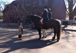 Looking up to the past.<br /><br />A young visitor finds both human and equine re-enactors equally fascinating andfriendly on Duke of Gloucester street.