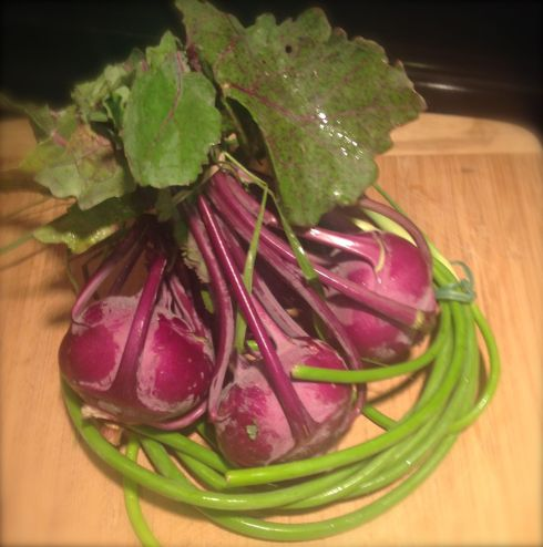 Purple kohlrabl nestled in a wreath of garlic scrapes